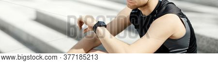 Checking Biological Rhythms Of Body. Guy In Sportswear Looking At Fitness Tracker On Arm, Sitting On