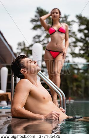 Selective Focus Of Muscular Man In Swimming Pool Near Woman In Swimsuit