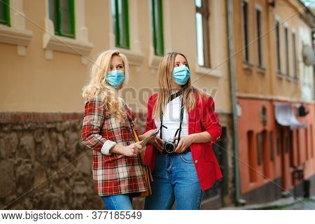 Friends Having Fun At Summer Vacations. Female Wearing Face Masks. Friends Traveling Together In Eur