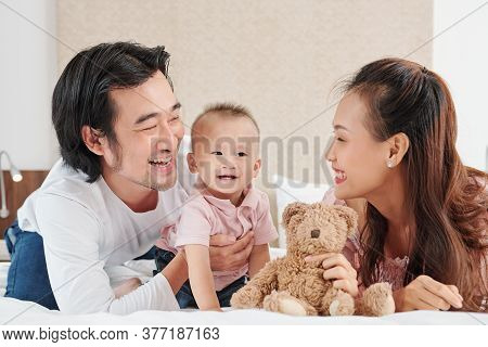 Happy Young Vietnamese Mother And Father Playing With Little Son In Bedroom