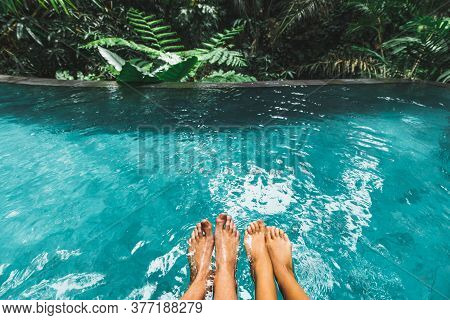 Couple Feet Together In Luxury Swimming Pool With Turquoise Clear Water Outdoors With Jungle View. T