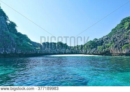 Secluded Beach In Thailand. A Semicircular Rocky Island And An Aquamarine Andaman Sea Enclose A Stri