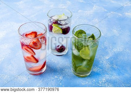 Three Glass Of Refreshing Cool Detox Drink With Strawberry, Lime, Cherry And Mint On Blue Background