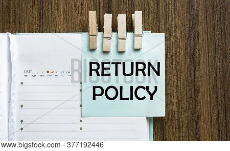 Return Policy Notes Paper And A Clothes Pegs On Wooden Background