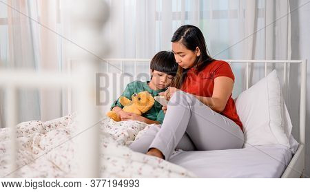 Asian Mother Work Home Together With Son. Mom And Kid Reading Fairy Tale Before Sleep On The Bed. Wo