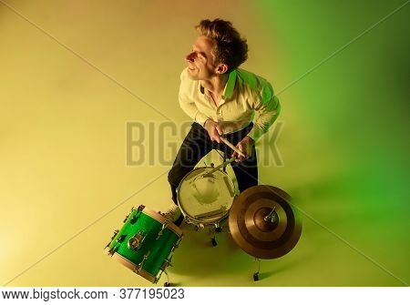 Top View. Young Caucasian Inspired And Expressive Musician, Drummer Performing On Multicolored Backg