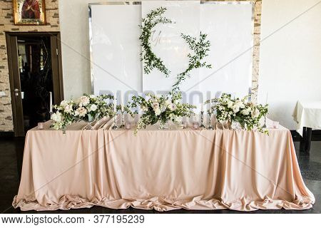 The Presidium Of The Newlyweds At The Wedding. Table For The Bride And Groom With Flowers And Candle