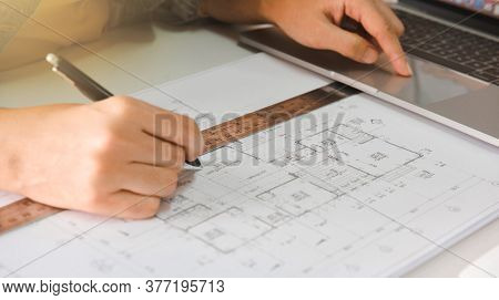 Engineers Holding A Pen Pointing To A Building And Using Laptop To Planning Project Schedule. Engine