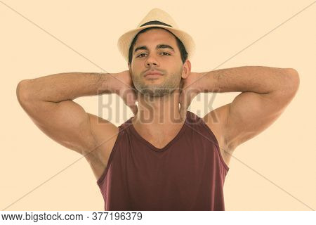 Studio Shot Of Young Handsome Hispanic Man With Both Arms Behind Neck