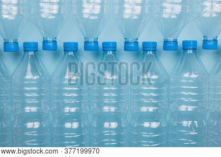 Horizontal Color Image With A Front View Of An Empty Clear Plastic Bottles With Caps Stacked On A Bl