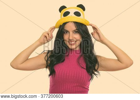 Studio Shot Of Young Happy Spanish Woman Smiling While Holding Hat With Both Hands