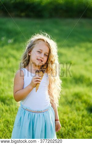 Little Blonde Girl With Long Hair Has Fun Eating Ice Cream In A Summer Park.