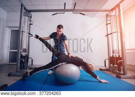 Concept Of Rehabilitation . Beautiful Young Woman Doing Exercises With Ball