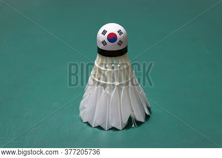 Used Shuttlecock And On Head Painted With South Korea Flag Put Vertical On Green Floor Of Badminton