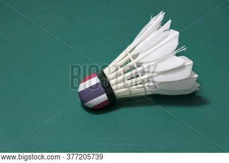 Used Shuttlecock And On Head Painted With Thai Flag Put Horizontal On Green Floor Of Badminton Court