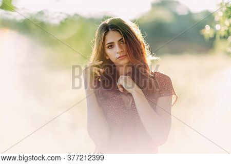 Portrait Of Beautiful Young Woman In With Long Brown Hair In Red Pattern Dress Posing Outdoors, Drea