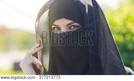 Migrant Woman From The East In Black Clothes Is Standing Against Bright Green Trees. A Migrant Woman