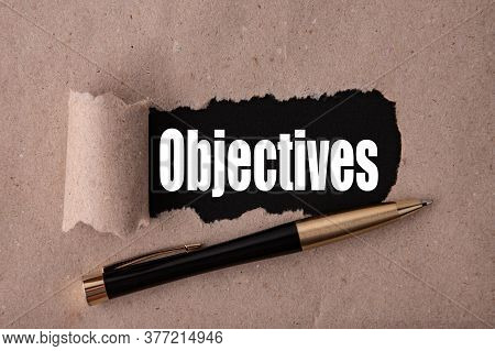 Objectives Text Written Under Torn Paper And A Recumbent Metal Pen. Business Strategy Concepts.