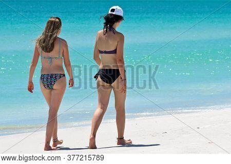 HOLMES BEACH, ANNA MARIA ISLAND, FL / USA - May 1, 2018: Two Beautiful Young Women taking a leisure walk on the Beach enjoying a Beautiful Summer Day.