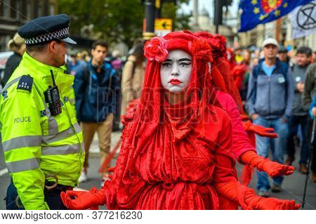 London - October 18, 2019: Close Up Of The Extinction Rebellion Red Brigade Protesters Passing A Met