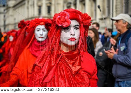 London - October 18, 2019: Close Up Of Red Brigade Protesters At An Extinction Rebellion Protest Mar