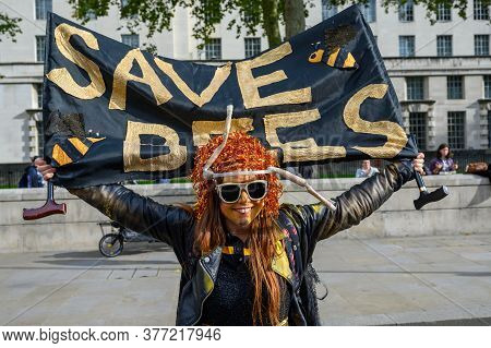 London - October 18, 2019: Extinction Rebellion Protester Holds A Save Bees Banner At An Extinction