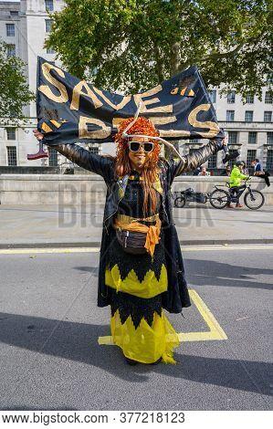 London - October 18, 2019: Full Length Vertical Shot Of Extinction Rebellion Protester Holding A Sav
