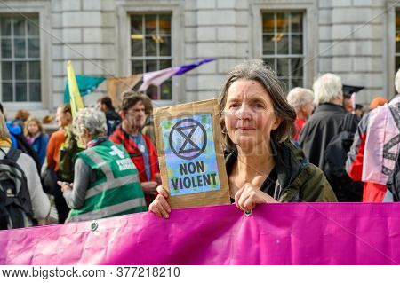 London - October 18, 2019: Middle Aged Female Extinction Rebellion Protester Holds A Non Violent Pro