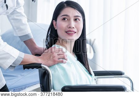 The Doctor's Hand Rests On The Shoulder Of The Female Patient Which Sat In A Wheelchair To Encourage