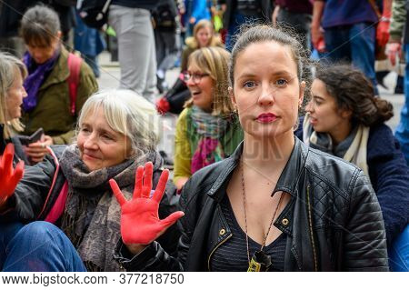 London - October 18, 2019: Female Extinction Rebellion Protester With Red Painted Hand Looks Directl