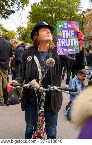 London - October 18, 2019: Vertical Shot Of Eccentric Extinction Rebellion Protester Holding A Prote