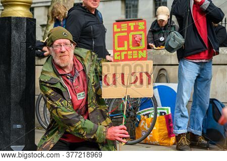 London - October 18, 2019: Mature Male Extinction Rebellion Protester Holding Home Made Signs At A P
