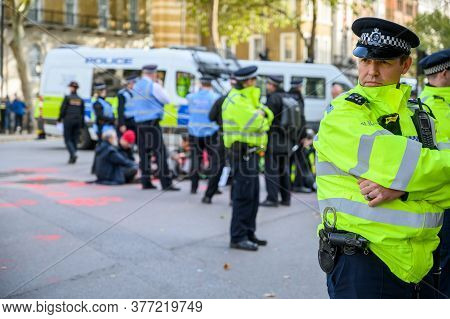 London - October 18, 2019: A Metropolitan Police Officer Stands Guard At An Extinction Rebellion Pro