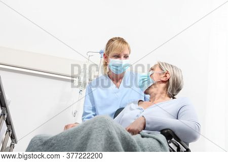 Nurse Take Comfort Elderly Woman In Wheelchair Wearing Surgical Protective Medical Masks In Hospital