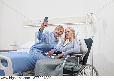 Nurse Helps With Cell Phone To Contact The Elderly Lady's Family In The Wheelchair Near Bed In Hospi