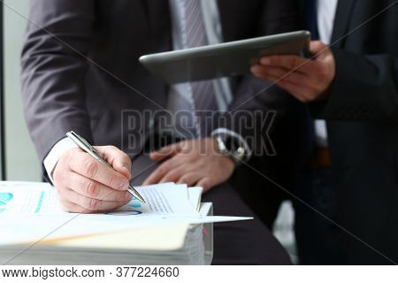 Cropped Head Close Up Of Man In Suit Writing On Paper While Manager Is Showing Touchpad To Him