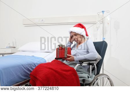 Christmas Day Isolated In Hospital Room With Coronavirus, Sad And Pensive Elderly Woman On Wheelchai