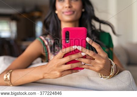 Close up hands of indian woman in traditional clothing holding smartphone. Hindu girl in sari with bracelets sitting on couch and using cellphone. Detail of indian girl hands typing message on mobile.