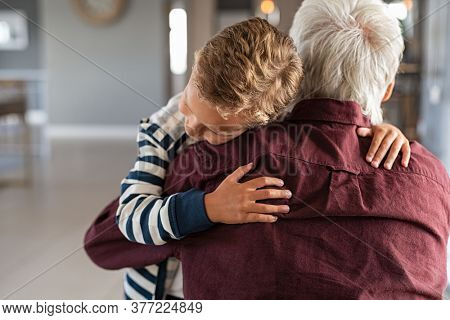 Back view of senior man embracing little boy at home. Lovely grandson hugging old granddad at home. Child embracing senior man while kneeling on floor, copy space.
