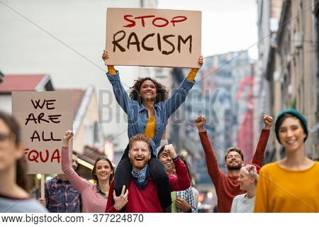Young group of men and women marching through the city during a Black Lives Matter protest. Group of multiethnic people on city street holding cardboard against racism during protest equality justice