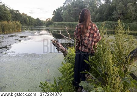 Silhouette Of A Girl In Nature. River Floodplain With Old Snags, Duckweed And Reeds. Untouched Natur