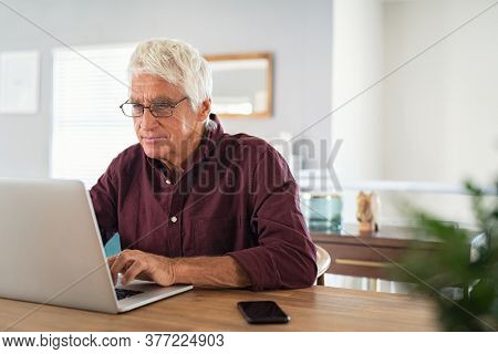 Old man working on laptop at home. Senior man using computer in living room, sitting on chair and looking at screen. Elderly grandfather wearing eyeglasses and working on laptop remotely.