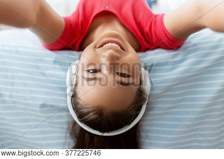 children and technology concept - portrait of smiling teenage girl in headphones lying on bed upside down and listening to music and taking selfie at home
