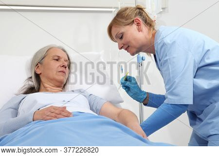 Nurse With The Syringe Injects The Vaccine To The Elderly Woman Patient Lying In The Hospital Room B
