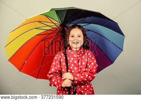 Fall Season. Kid Girl Happy Hold Colorful Rainbow Umbrella. Rainy Weather With Proper Garments. Rain