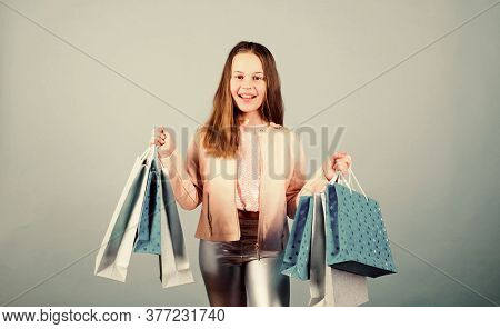 Happy Child In Shop With Bags. Shopping Day Happiness. Buy Clothes. Birthday Girl Shopping. Fashion