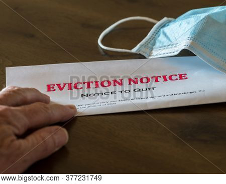 Defaulting Renter With Facemask Receives Letter Giving Notice Of Eviction From Home On Wooden Table