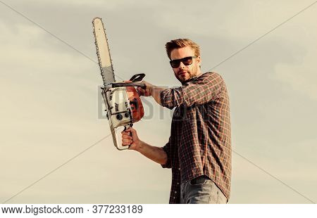Sharp Blade. Handsome Man With Chainsaw Blue Sky Background. Gardener Lumberjack Equipment. Lumberja