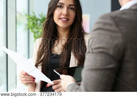 Waist Up Portrait Of Smiling Young Female Standing With Papers And Communicating With Male Using Tou