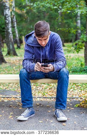 Young Man With A Phone Sit On The Bench In The Autumn Park